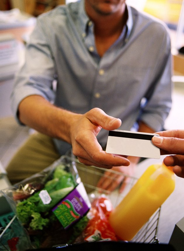 Close-up of a man's hand giving a credit card to a shopkeeper in a supermarket