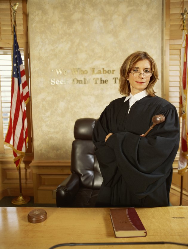 Portrait of a judge standing with her arms folded, holding the gavel