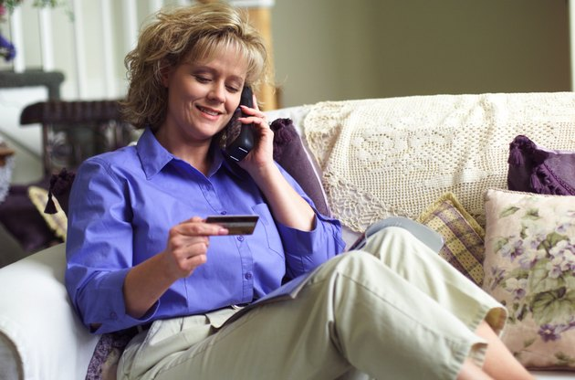 a blonde caucasian woman uses a credit card to purchase over the phone