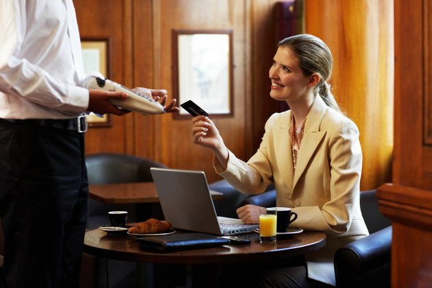 Young businesswoman at cafe table, paying waiter by credit card