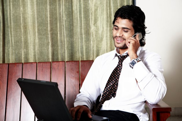 Young man using laptop and mobile phone