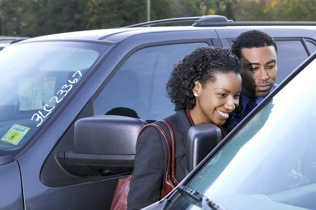 A couple looks at purchasing a new car in a car lot