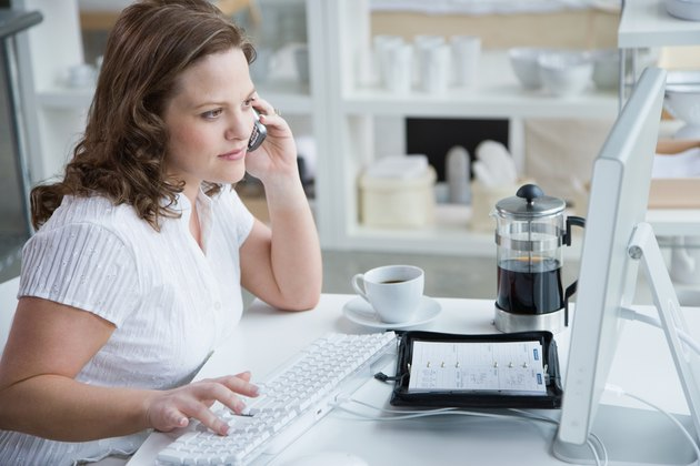 Woman sitting at desk with computer and cell phone