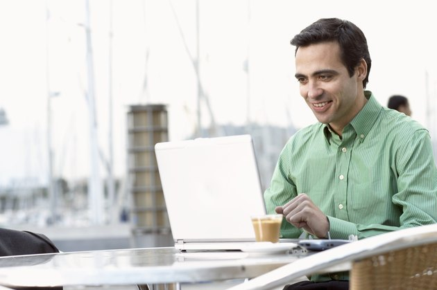 Businessman sitting at table outdoors using laptop