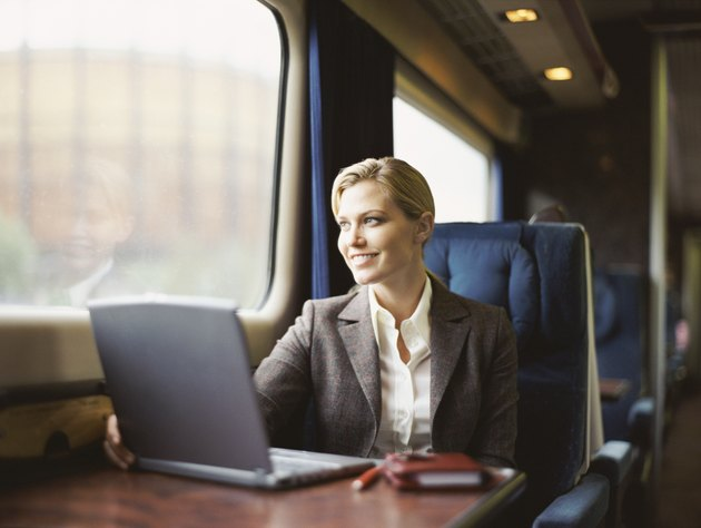Businesswoman Sitting in a Train With a Laptop on a Table