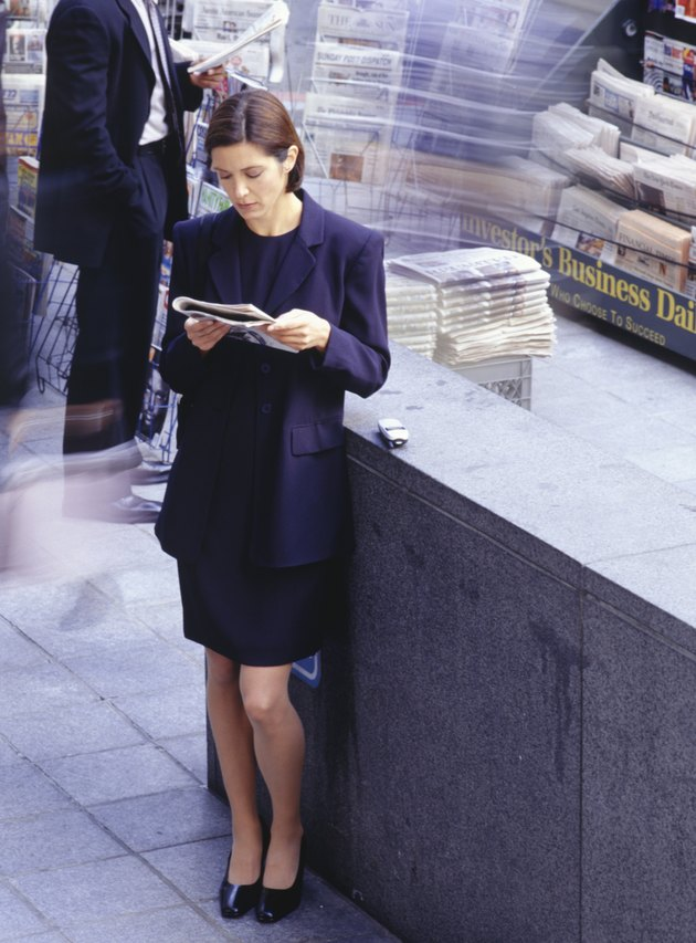 Businesswoman standing by news stand, reading newspaper
