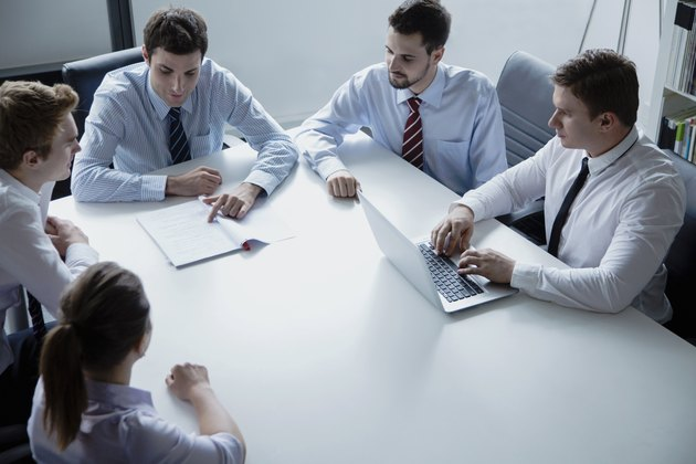 Five business people having a business meeting at the table in the office
