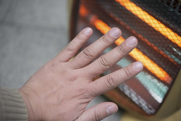 heating up a hand in front of an electric heater
