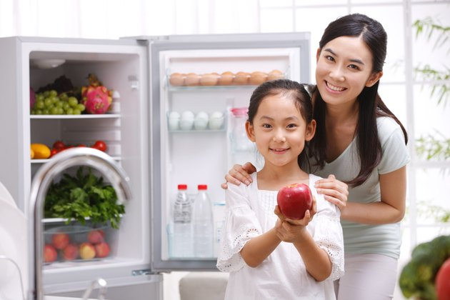 Mother and daughter holding apple in kitchen