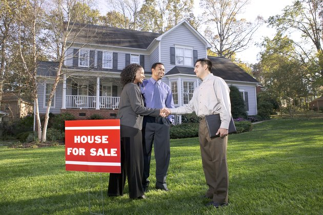 A real estate agent shakes hands with a woman as the couple has decided to purchase a suburban home