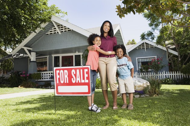 Mother and children with For Sale sign in front of house