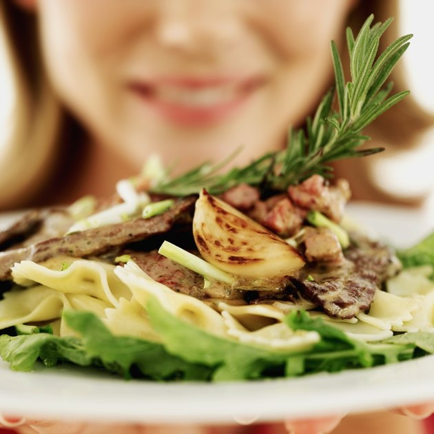 close-up of a young woman holding a plate of steak with pasta and vegetables