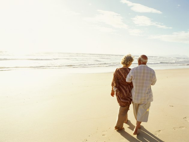 Senior couple walking on beach, rear view