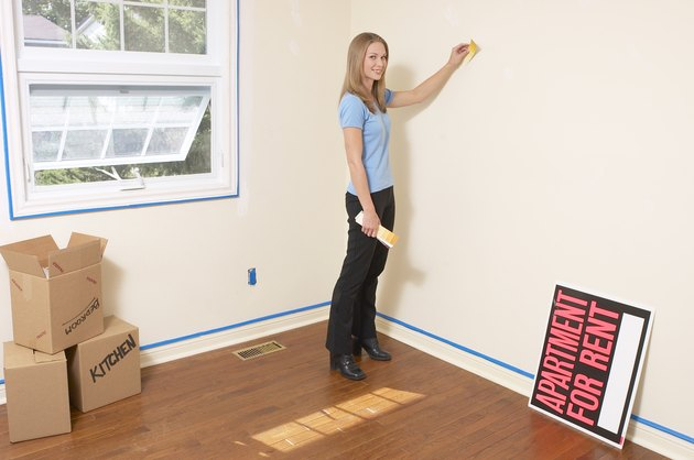 Young woman standing in an apartment holding a color swatch against the wall