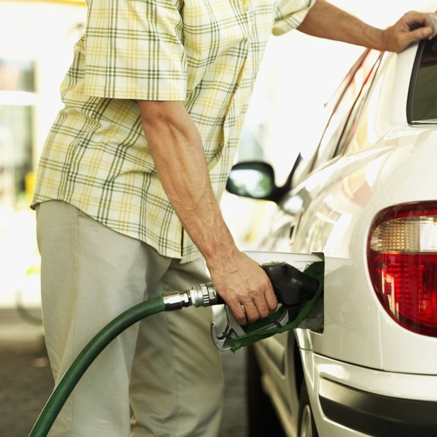 mid section view of a man filling petrol into a car