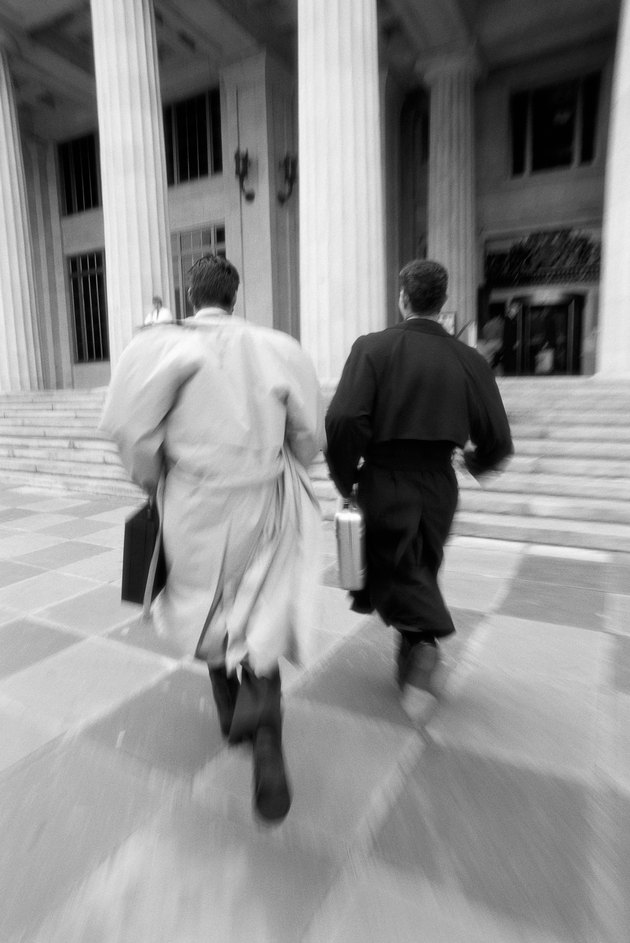 black and white portrait of two young businessmen running