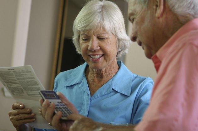 Senior man using a calculator with a senior woman sitting beside him