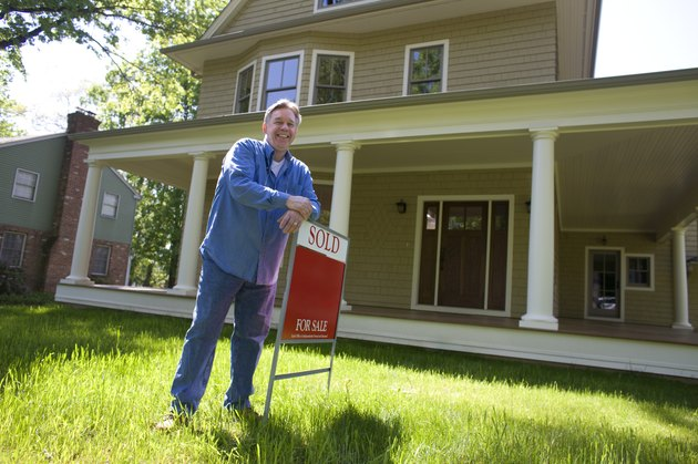 Man standing with for sale sign in front of home