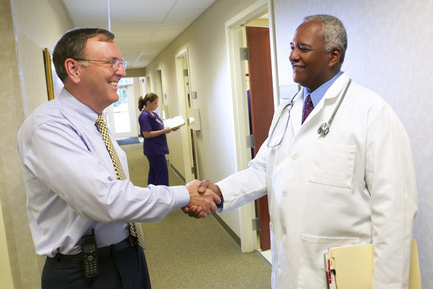 An administrator and doctor shake hands in the hall of a doctor's office