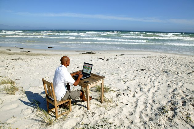 Dark-skinned bald man working at his desk on the beach