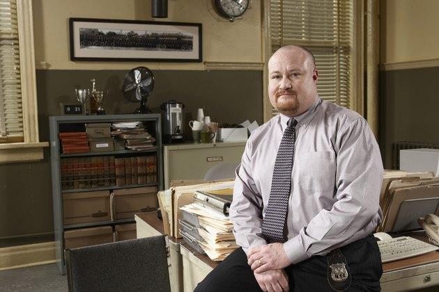 Man sitting on desk in office, portrait