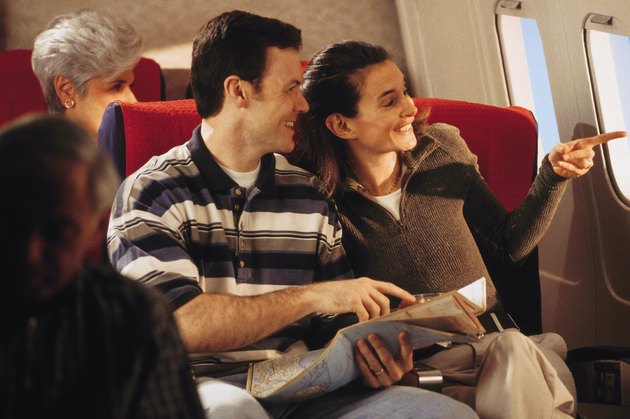 Couple looking out window of airplane