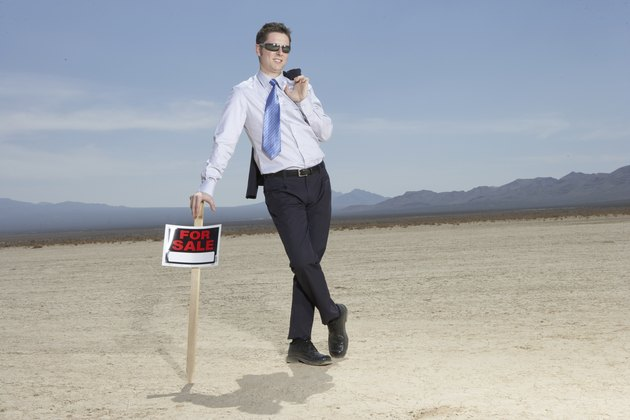 Businessman in dry lake bed leaning on 'for sale' sign