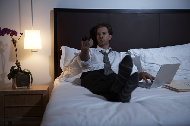 Businessman lying on bed using laptop and remote control