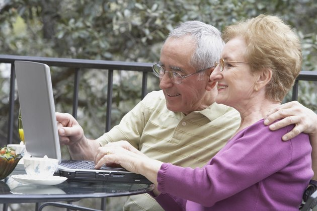 Senior couple sitting at a table in front of a laptop
