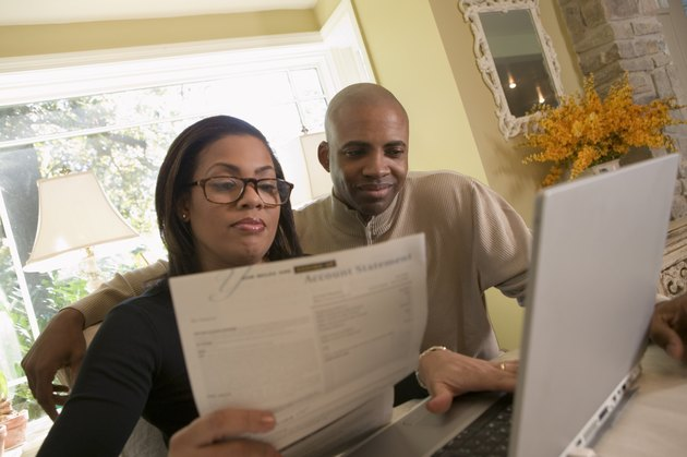Couple with paperwork and laptop