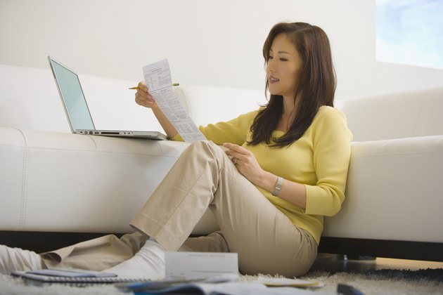 Woman sitting on floor paying bills