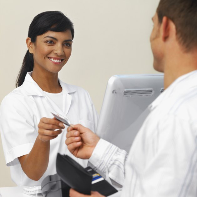 Close-up of patient paying dental nurse with credit card