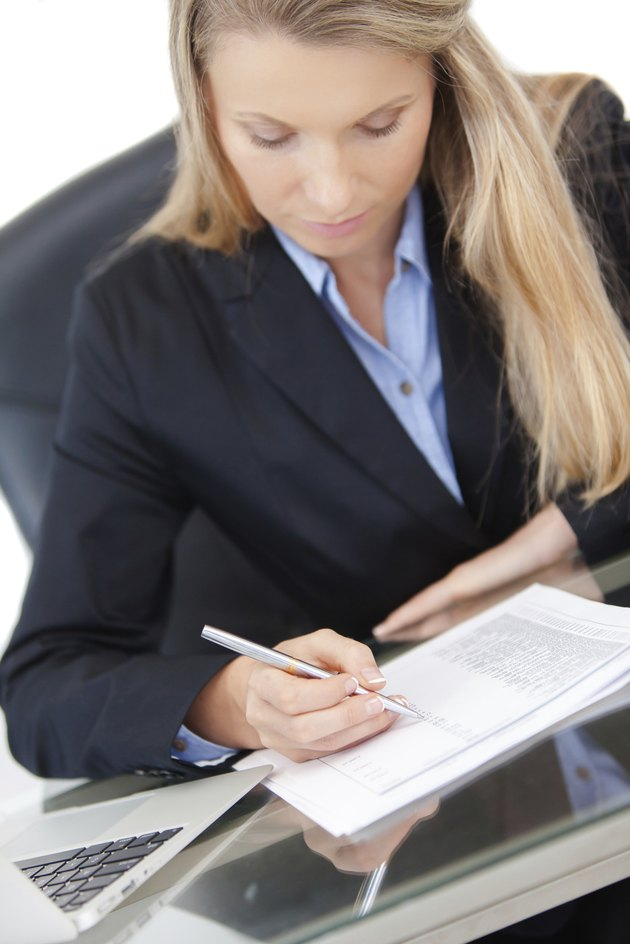 Close-up of working businesswoman at the desk