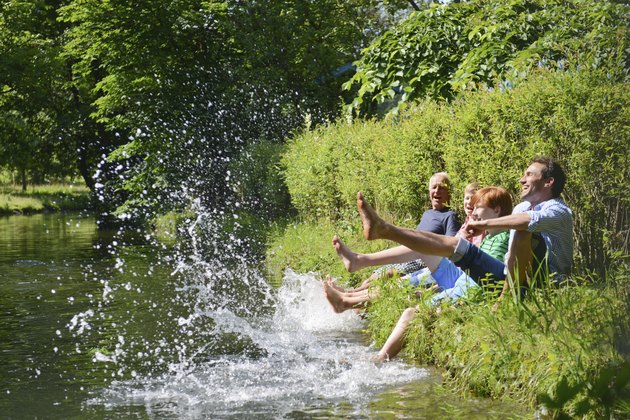 Multigenerational family splashing water from riverbank