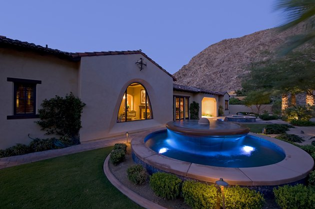 House exterior with fountain in garden at dusk