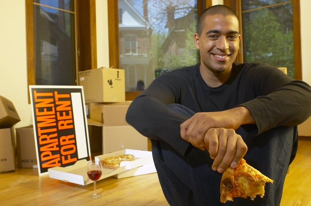 Man eating pizza in new apartment