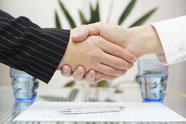 businessman and businesswoman shaking hands over signed contract.