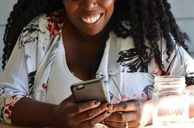 Black woman smiling looking at phone