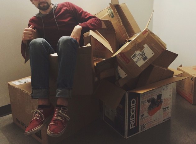 Young man sitting in empty moving boxes