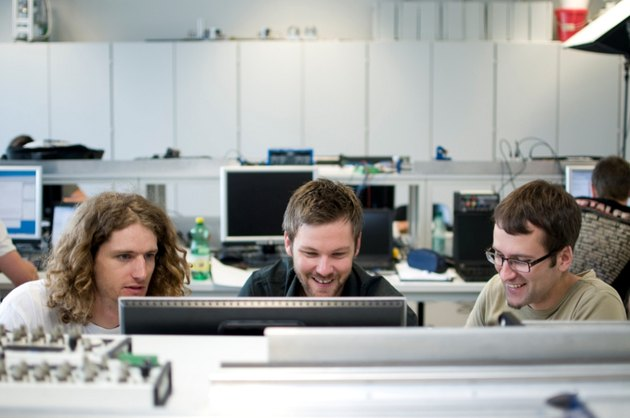 Three white guys working around a computer monitor