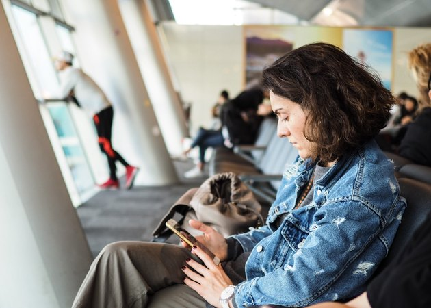 Young woman reading phone at airport gate