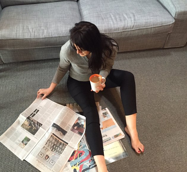 Woman reading newspaper sitting on the floor