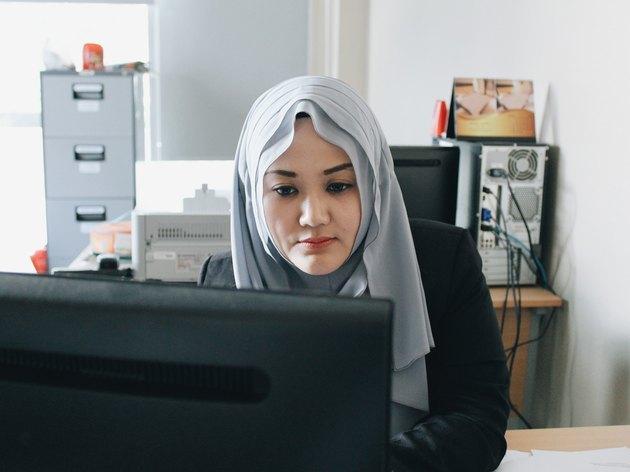 Hijabi working at desktop computer