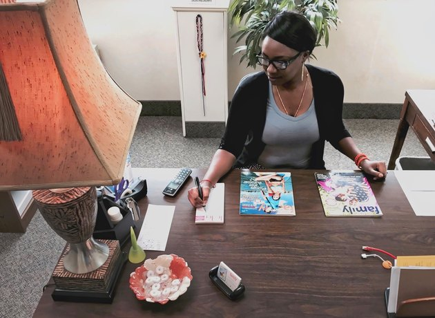 Young Black woman working at desk in office