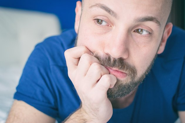 Young white man with blue shirt and beard looking thoughtful