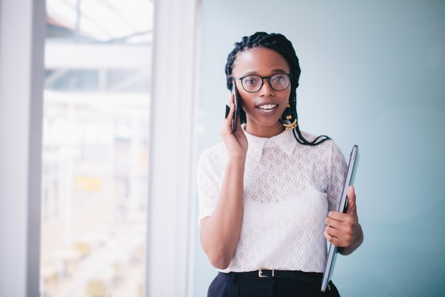 Young Black woman in business attire on phone