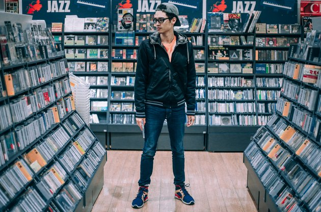 Young man standing between rows of CD racks in music store