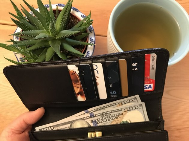 An open wallet, cup of tea, and succulent