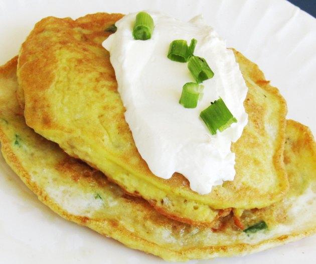 2 potato pancakes topped with sour cream and scallions.