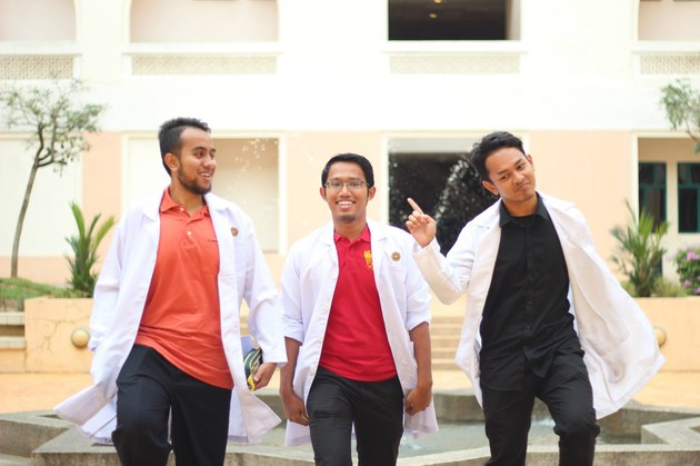 Three pharmacy students in white lab coats
